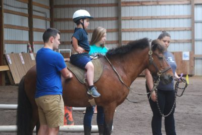 A child experiencing Therapeutic Riding